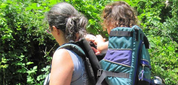 a woman and her toddler daughter hiking together, the little girl is in a hiking carrier on the woman's back