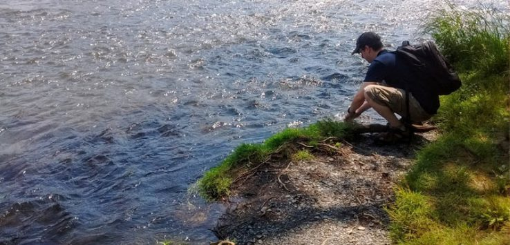 hiker with backpack crouches down by water