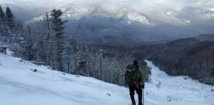 man hiking in snow looking out at mountains
