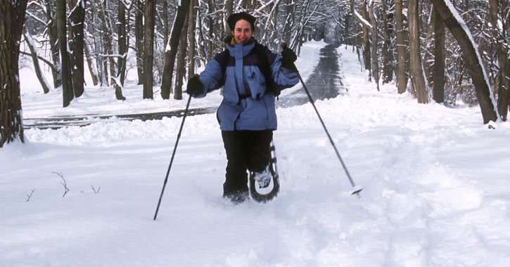 a woman walking with snowshoes and ski poles through the snow, smiling at camera, trees and road behind her