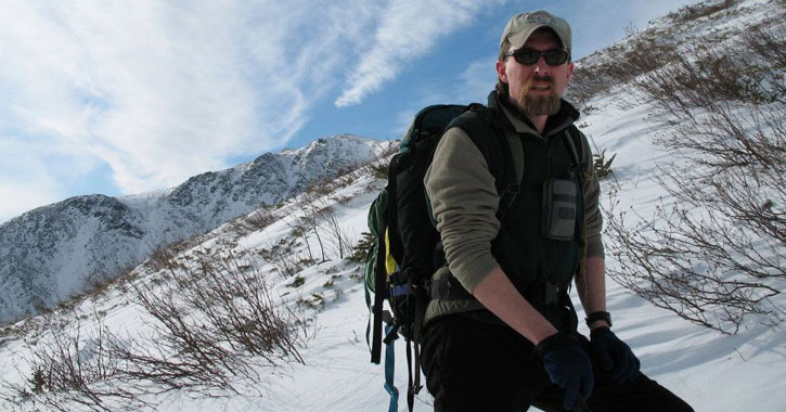 a hiker out in the winter, posing for camera