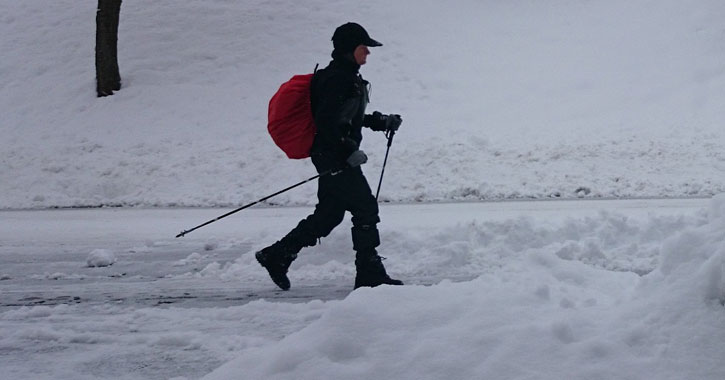 person winter hiking with trekking poles