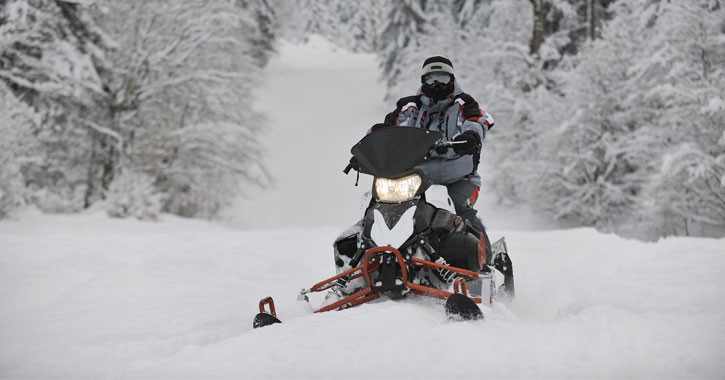 person on snowmobile looking right at the camera, surrounded by snow and trees