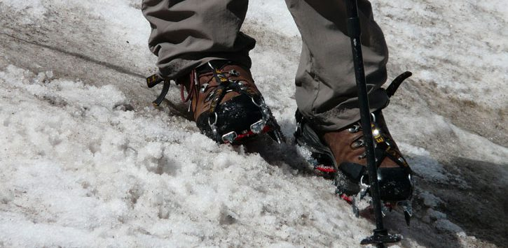 close up of someone's feet in crampon's as the hike in the winter