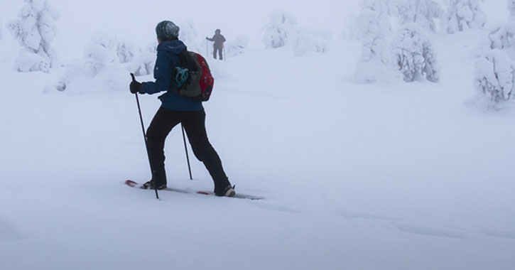 man cross-country skiing through snow, another skier in the background
