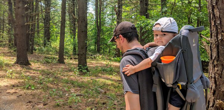 man hiking with toddler in a hiking backpack