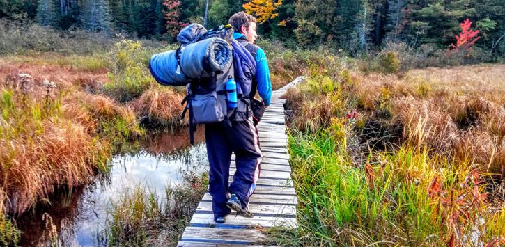 man hiking over small bridge surrounded by fall foliage