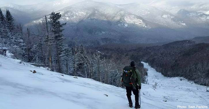 hiker standing on mountain in the winter