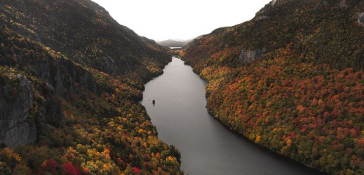 waterway near mountains with fall colors