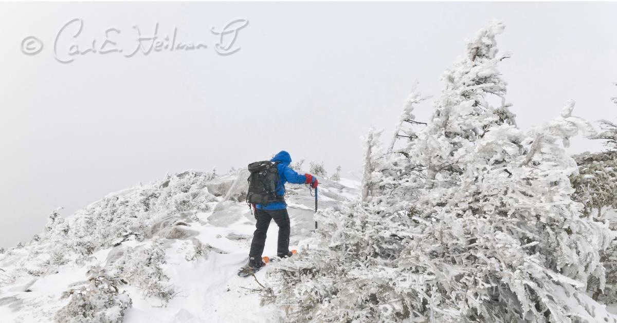 man snowshoes up mountain