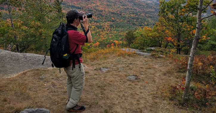 Man taking a photo during a hiking trip
