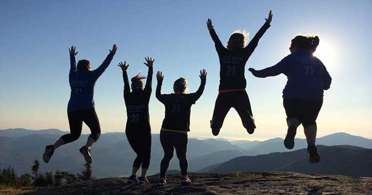 Hikers jumping for joy after reaching the summit