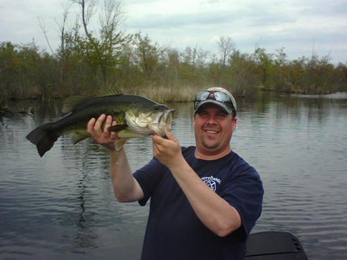 Man in blue shirt holding large bass