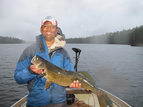 Man on adirondack lake holding large fish