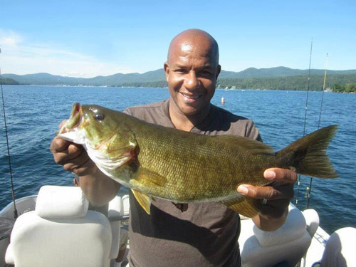 Man in boat on Lake George holding large fish