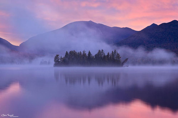 An island on a lake with mountains in the distance during a pink sunrise