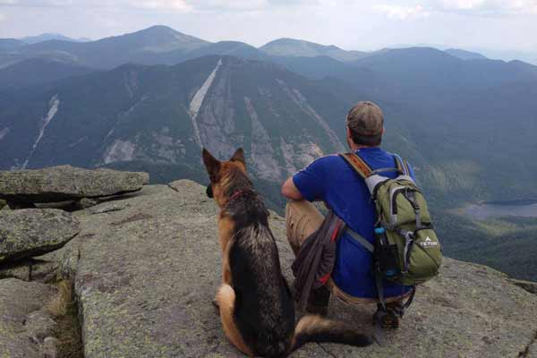 Hiker and german shepherd enjoy view from rocky ledge