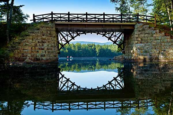 Old stone bridge over still water
