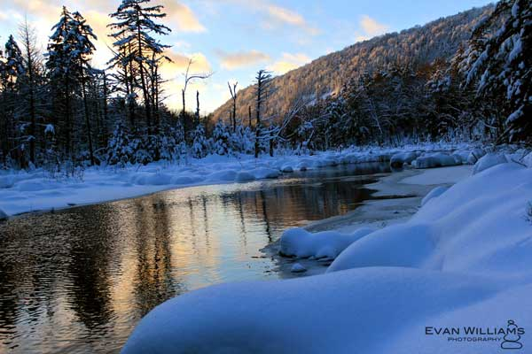 Sunset over a river lined with snow and trees