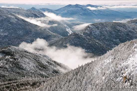 Snow covered mountain peaks with low cliuds in the valleys