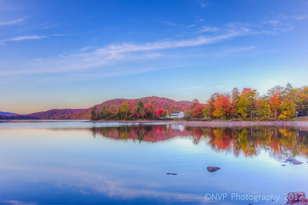 Still lake lined by brilliant red fall foliage