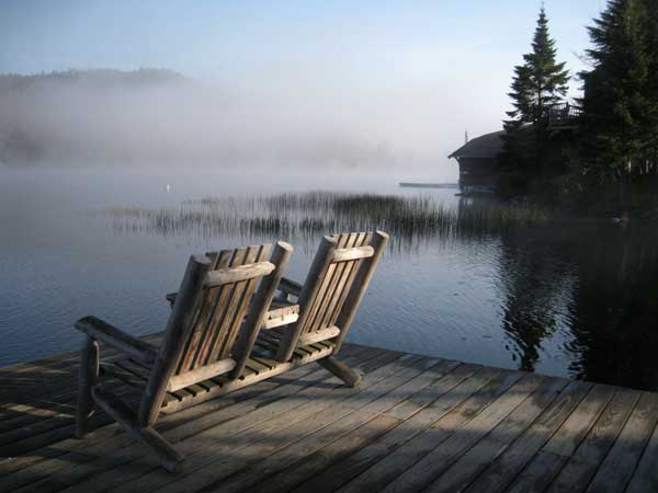 Adirodnack chairs sitting on a dock overlooking a foggy lake