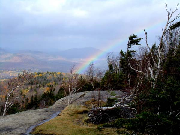 a rainbow at the summit of a mountain