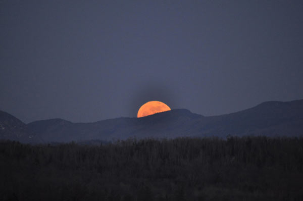 Golden moon rises over Mountain ridge
