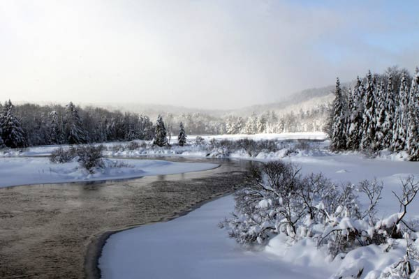 Snowy landscape surrounds a river