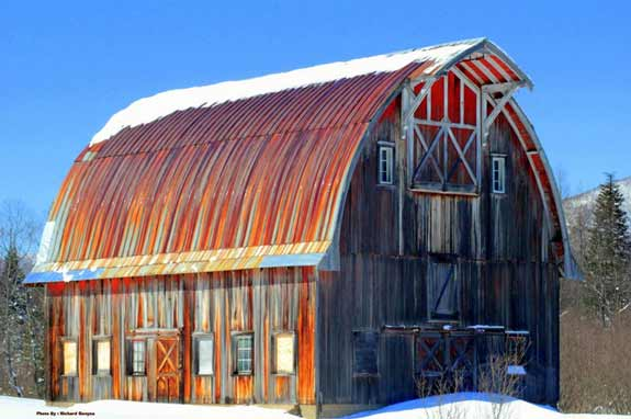 Weathered red and grey barn in winter