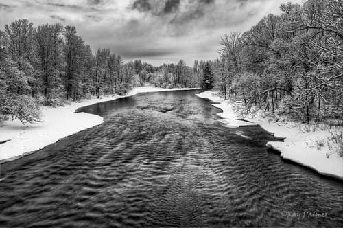 rippling water of the Saranac River in winter lined by snow covered trees
