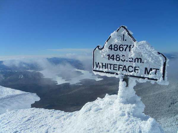 Snowy sign marking summit of whiteface mountain overlooking Lake Placid