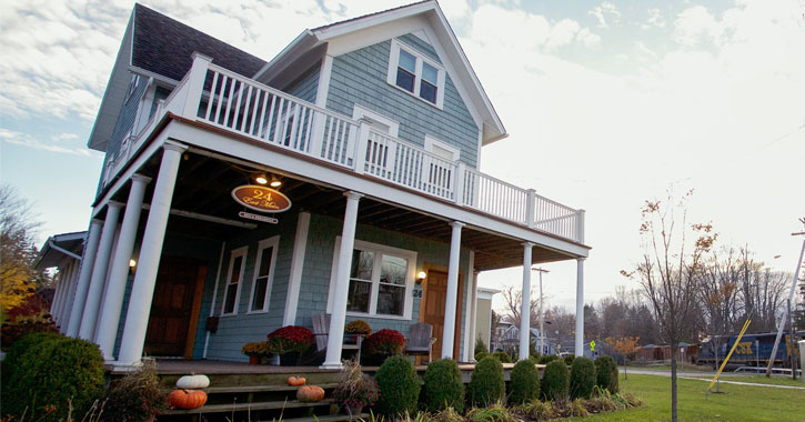 a light blue bed and breakfast with pumpkins on the porch