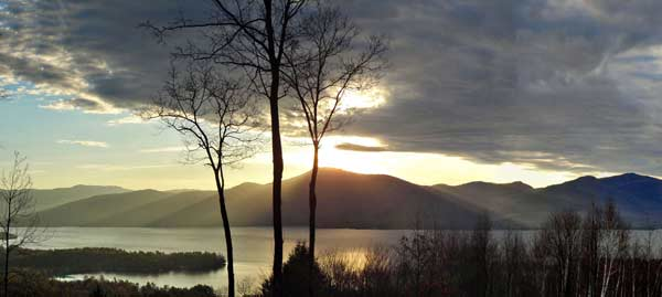 sun rays shining onto lake george from behind a mountain