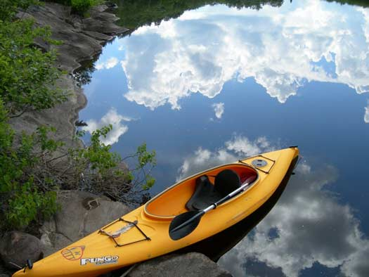 a yellow kayak on the edge of very still, reflective waters