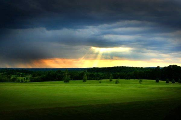sun rays breaking through a cloudy sky over a green field