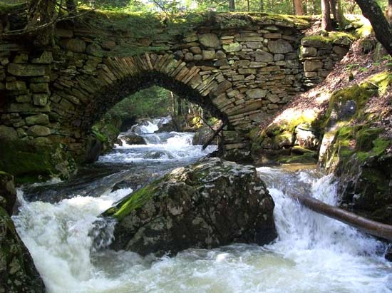 Rushing waters under a stone bridge
