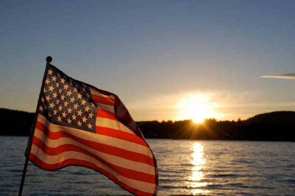 American flag against the sunset over a lake
