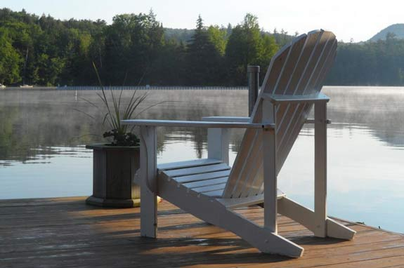 white adirondack chair on a dock overlooking water