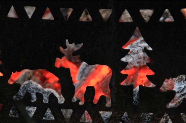 Bright red embers behind a fire grate with bear, moose, and tree shaped openings