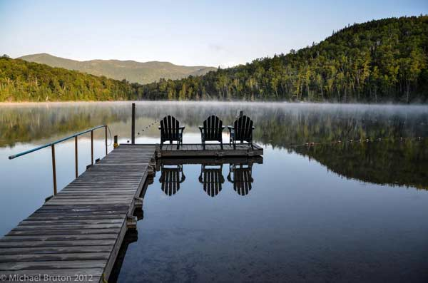 3 Adirondack chairs on a dock over still lake