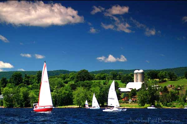 Sailboats on Great Sacandaga Lake in front of a lakeshore farm