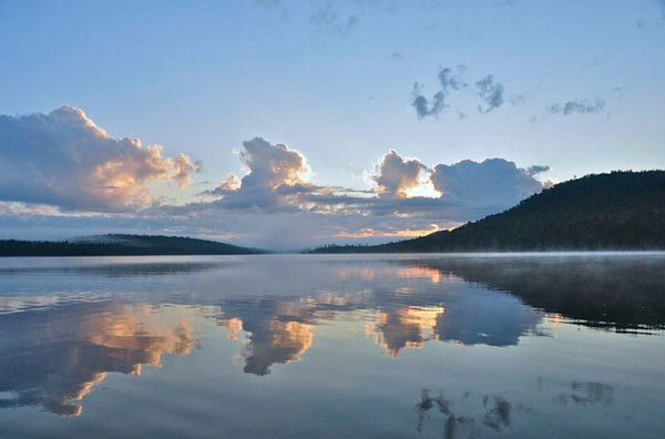 Clouds reflecting on Raquette Lake in the early morning