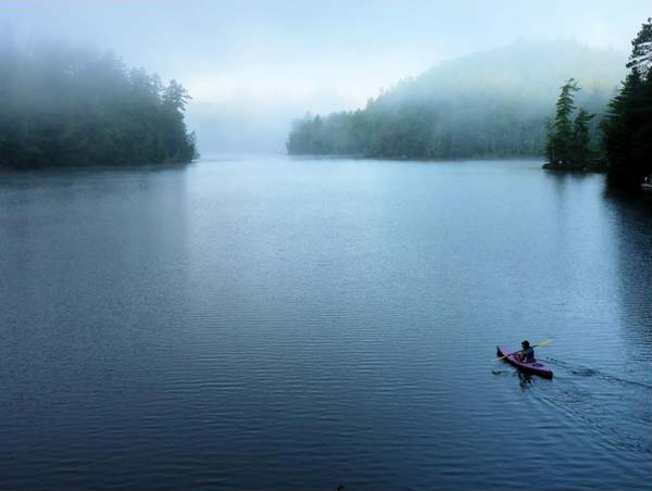 lone kayaker paddles on a foggy lake
