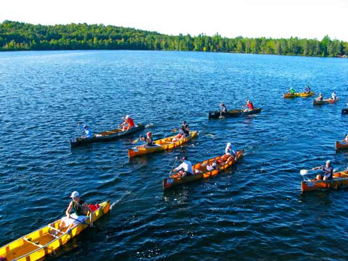 a group of canoes paddling along a lake