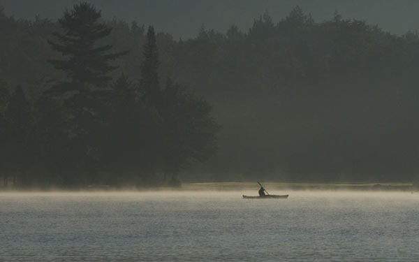 Lone kayaker paddling on a foggy morning