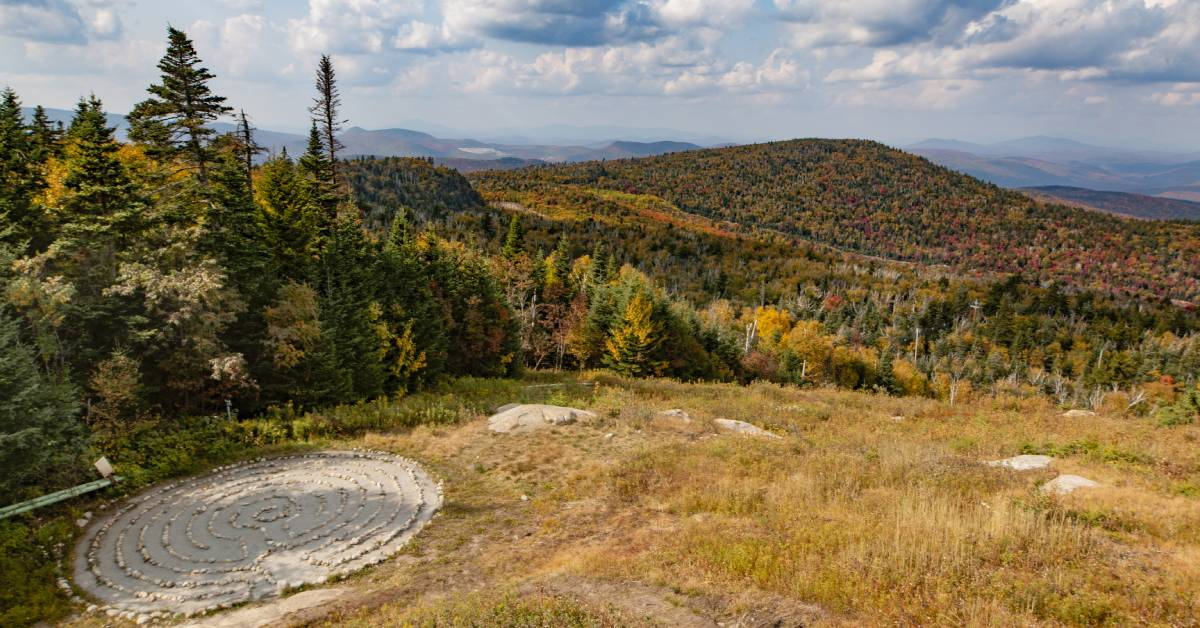 overhead view of a stone labyrinth and fall colors on trees and mountains