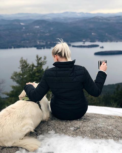 golden retriever and woman on mountain summit