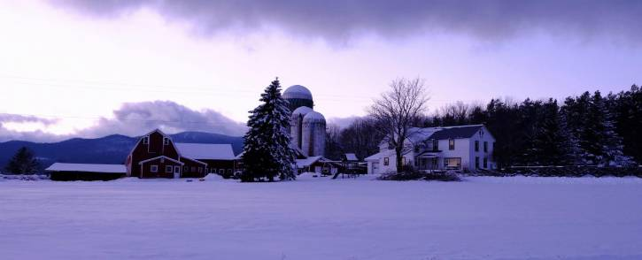 House and farm covered in snow & distant mountains