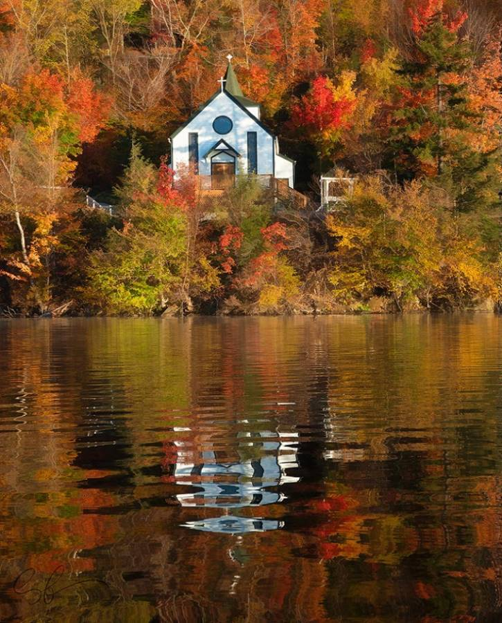 Small chapel on a lake surrounded by fall foliage